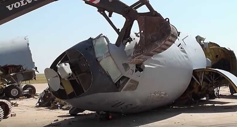 Excavator crushing the front fuselage of a jetliner